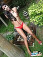 Small tits Poy strips red bodystocking in garden under parasol